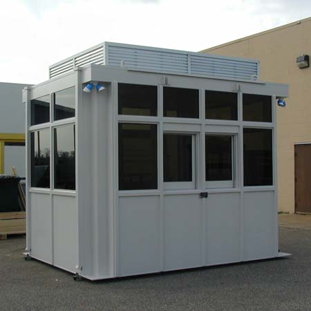 Guard House Bullet Resistant preassembled.  Glass awnings ship loose and reattached in field.  Louvered wall atop hides roof mounted air conditioners.